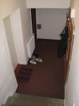Předsíň - Pohled od vchodových dveří. Prvními dveřmi vlevo se vstupuje přes kuchyňku do modlitební místnosti. Vpravo dole, za zrcadlem a věšáky, je WC.
