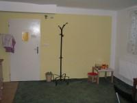 Kuchyňka - Dveře, kterými se vstupuje z předsíně. Vpravo je malý dětský koutek, vlevo kuchyňská linka.