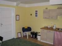 Kuchyňka - Dveře, kterými se vstupuje z kuchyňky do modlitební místnosti. Vpravo je kuchyňská linka.