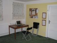 Kuchyňka - Dveře, kterými se vstupuje z kuchyňky do modlitební místnosti. Vlevo je stůl s notebookem, kde je možno si rezervovat modlitební místnost a zjistit, kdo má rezervovanou následující hodinu.